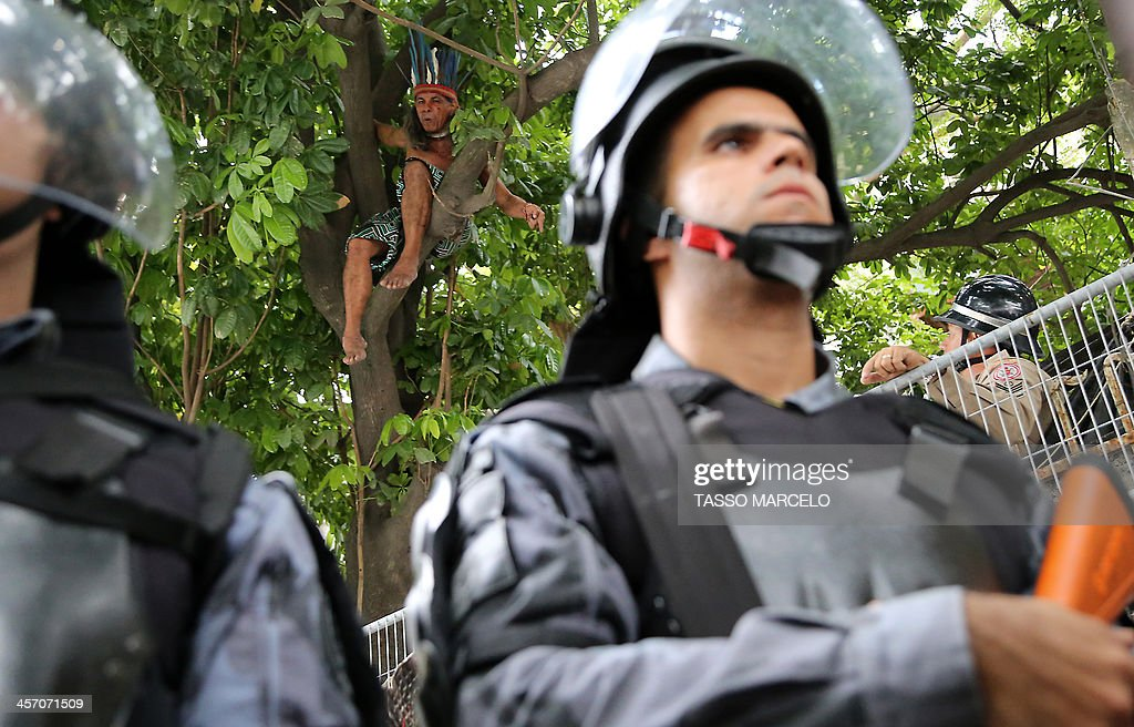 An indigenous activist climbs up a tree during a demonstration at the Museu do Indio (Indian Museum) 'Aldea Maracana' (Maracana Village) in Rio de Janeiro, Brazil, on December 16, 2013. The demonstrators, among whom there were some 30 Amazonic natives, seized the museum protesting against its scheduled demolition to continue the works in the Mario Filho 'Maracana' stadium ahead of the FIFA WC Brazil 2014.