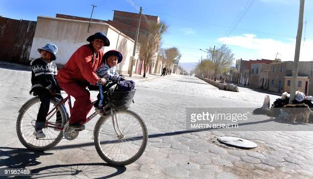 An indigenous Bolivian woman rides her bike with her children in Uyuni Bolivia near the Uyuni salt flats on October 9 2009 The Uyuni salt flats are...