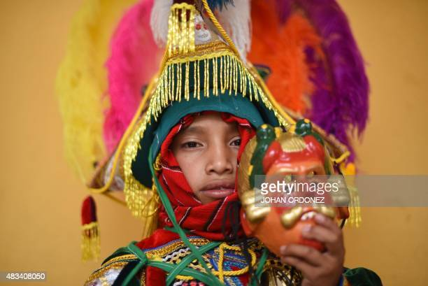 An indigenous child dressed for the Dance of the Conquerors poses during the annual fair in honor of the 'Virgen del Transito' in Joyabaj...