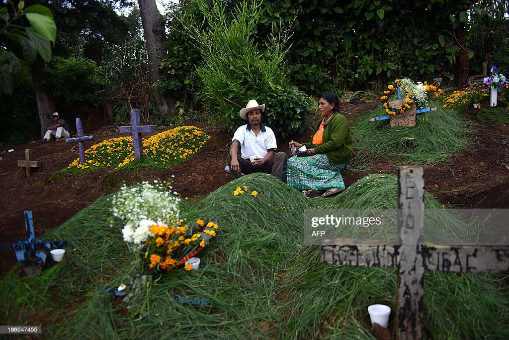 An indigenous couple chat after adorn the grave of a relative at the municipal cemetery of Sumpango, Sacatepequez departament, some 48 km west of Guatemala City, on All Saints' Day on November 1, 2013. AFP PHOTO/Johan ORDONEZ