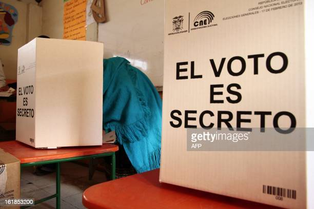 An indigenous Ecuadorean votes in Cangahua 45 km northeast of Quito on February 17 2013 Ecuadorans cast ballots Sunday in national elections expected...