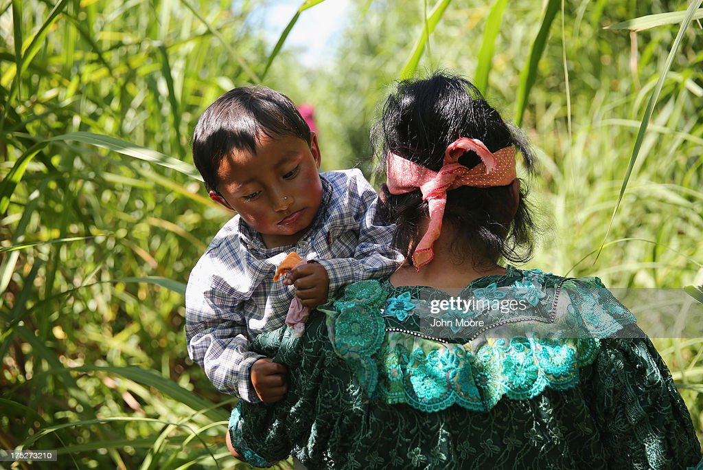 An Indigenous family walks from Guatemala into Mexico after illegally crossing the border at the Suchiate River on August 1 2013 in Talisman Mexico...