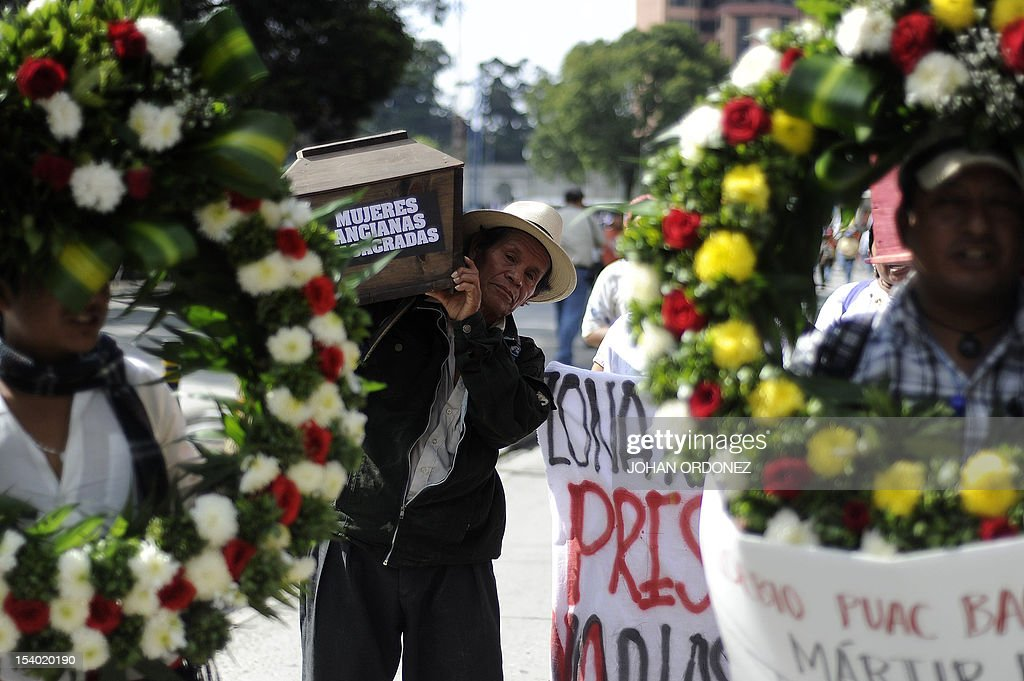 An indigenous man carries a mock coffin during a protest in Guatemala City on October 12 2012 The protest took place as a reaction to the eight...