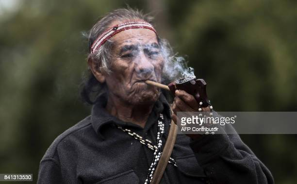 An indigenous man from a Guarani tribe smokes his pipe in the Pico de Jaragua national reserve in Sao Paulo Brazil on August 31 2017 A group of...