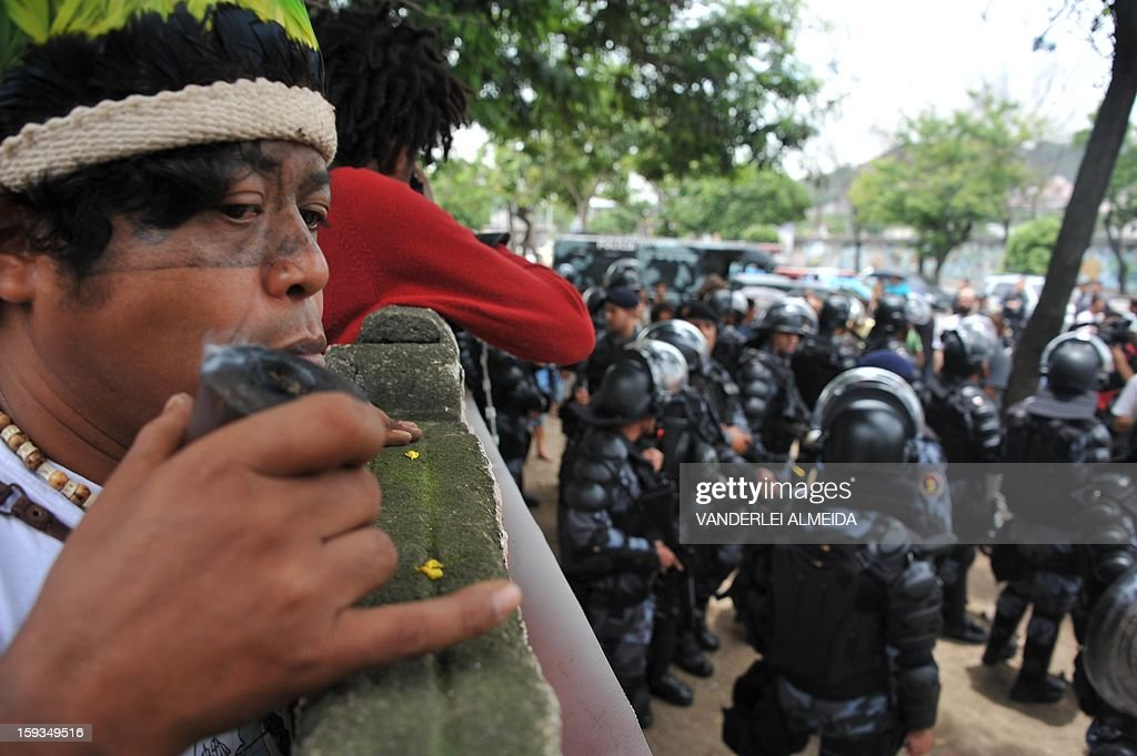 An indigenous man looks over a fence as riot police officers stand guard at the entrance of the old indigenous museum --aka Aldea Maracana-- next to Maracana stadium in Rio de Janeiro on January 12, 2013. Indians have been occupying the place since 2006 as a protest against Rio de Janeiro's governmet decision to throw them out and pull down the building to construct 10,500 parking lots for the upcoming Brazil 2014 FIFA World Cup.