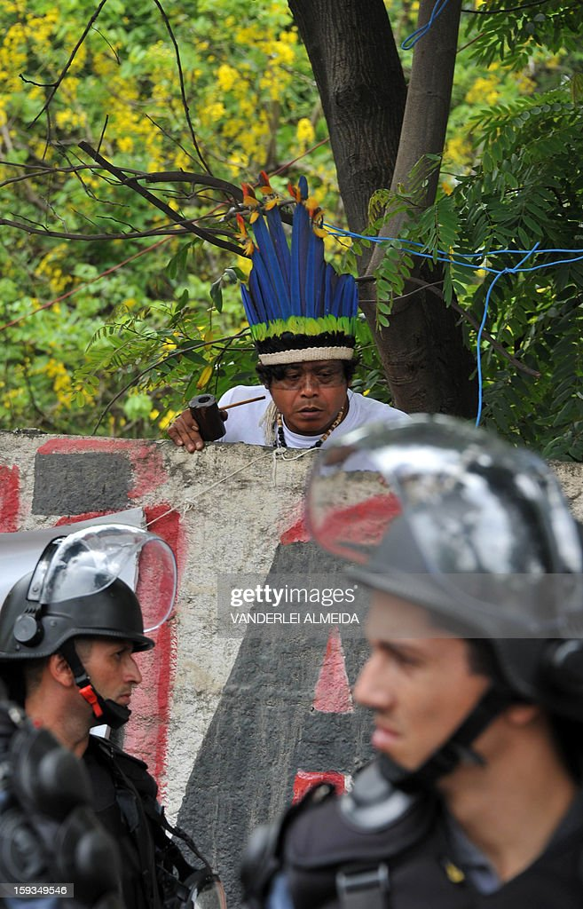An indigenous man looks over a fence as riot police officers stand guard at the entrance of the old indigenous museum --aka Aldea Maracana-- next to Maracana stadium in Rio de Janeiro on January 12, 2013. Indians have been occupying the place since 2006 as a protest against Rio de Janeiro's governmet decision to throw them out and pull down the building to construct 10,500 parking lots for the upcoming Brazil 2014 FIFA World Cup. AFP PHOTO/VANDERLEI ALMEIDA