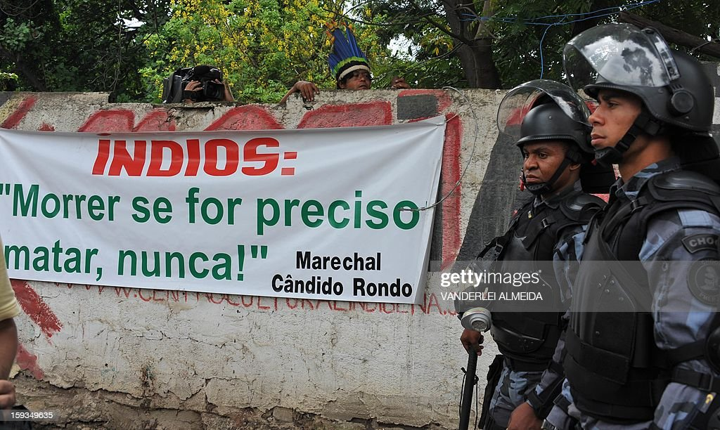 An indigenous man looks over a wall as riot police officers stand guard at the entrance of the old indigenous museum --aka Aldea Maracana-- next to Maracana stadium in Rio de Janeiro on January 12, 2013. Indians have been occupying the place since 2006 as a protest against Rio de Janeiro's governmet decision to throw them out and pull down the building to construct 10,500 parking lots for the upcoming Brazil 2014 FIFA World Cup. AFP PHOTO/VANDERLEI ALMEIDA