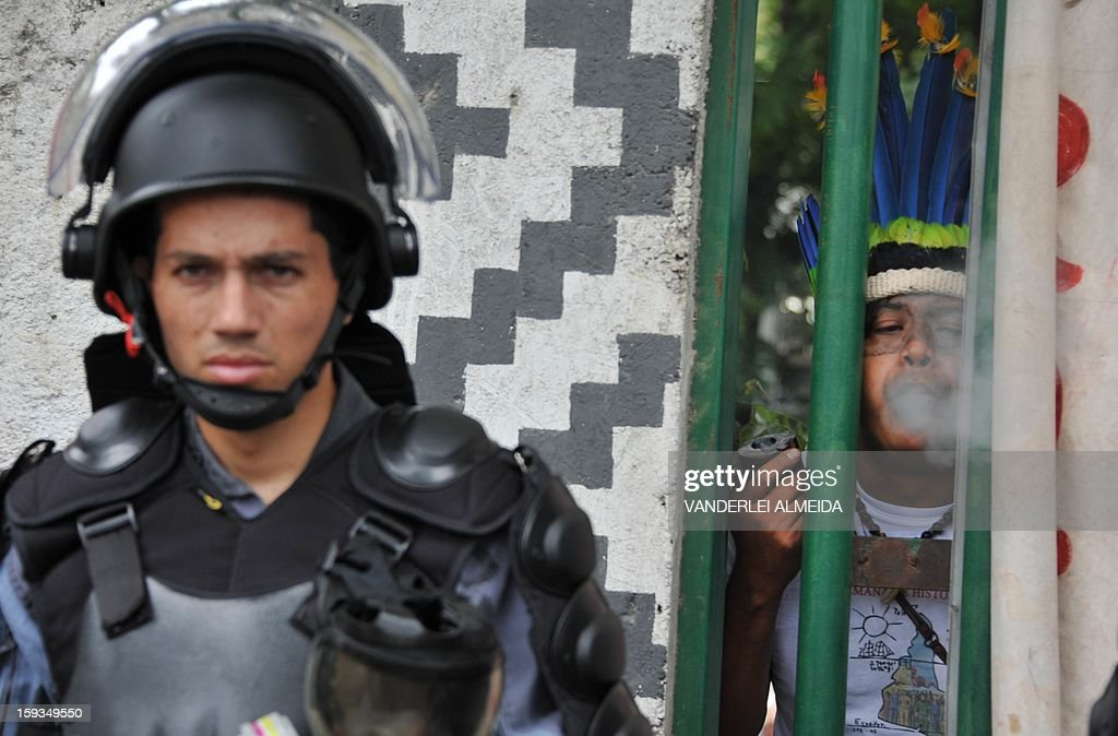 An indigenous man throws smoke at riot police officers standing guard at the entrance of the old indigenous museum --aka Aldea Maracana-- next to Maracana stadium in Rio de Janeiro on January 12, 2013. Indians have been occupying the place since 2006 as a protest against Rio de Janeiro's governmet decision to throw them out and pull down the building to construct 10,500 parking lots for the upcoming Brazil 2014 FIFA World Cup. AFP PHOTO/VANDERLEI ALMEIDA