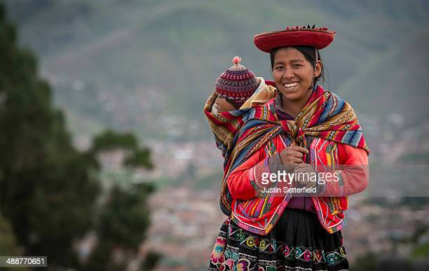 An indigenous Peruvian woman carries her child through Sacsayhuaman above the Incan city of Cusco on January 13 2014 in Cusco Peru The historic town...