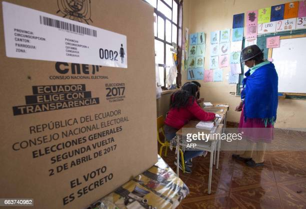 An indigenous woman from Cangahua northeast of Quito prepares to vote during the presidential runoff election on April 2 2017 Ecuadoreans headed to...