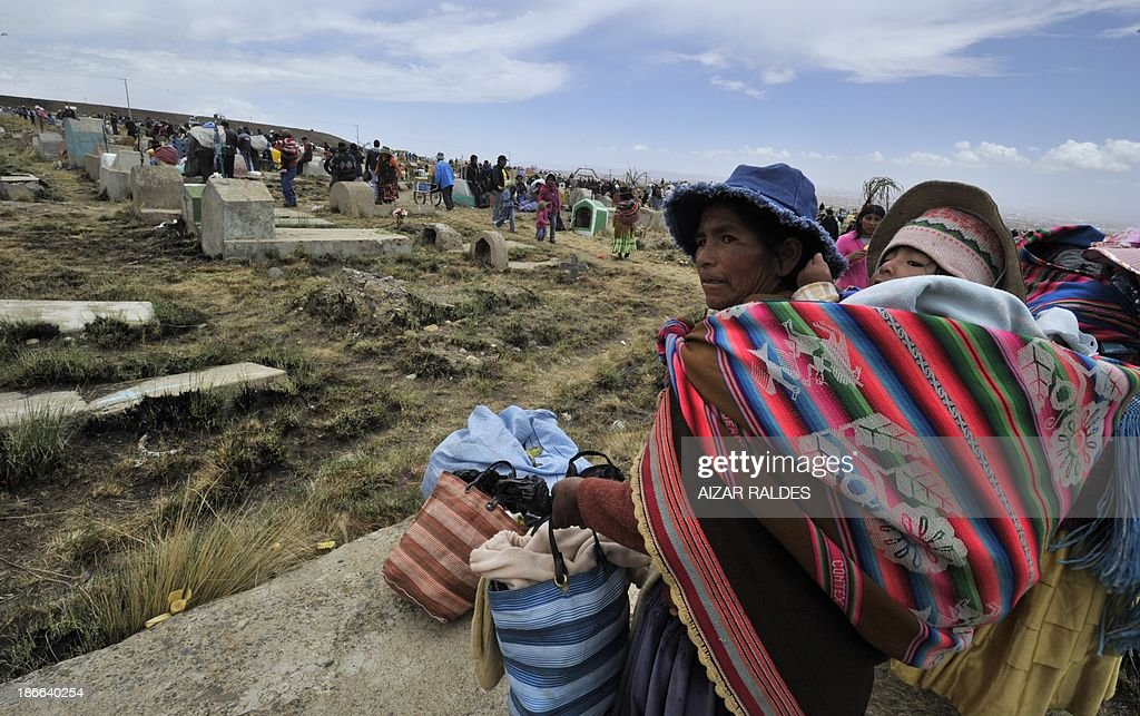 An indigenous woman walks with a baby at Villa Ingenio cemetery in El Alto, 25 Km west of La Paz, on November 2, 2013, during the commemoration of the day of the dead. The traditional Catholic holiday honors the dead and is celebrated annually. AFP PHOTO/Aizar Raldes