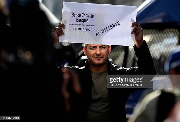 An indignant holds a letter for the European Central Bank as he takes part in a protest against the Bank of Italy in the centre of Rome on October 12...