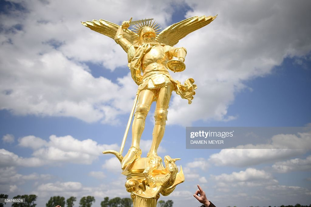 An individual points at the statue of the Archangel Michael, regilded and restored with a new lighting rod, on the eve of its placement back atop the Mont Saint-Michel Abbey on May 25, 2016 in Mont Saint-Michel. / AFP / DAMIEN