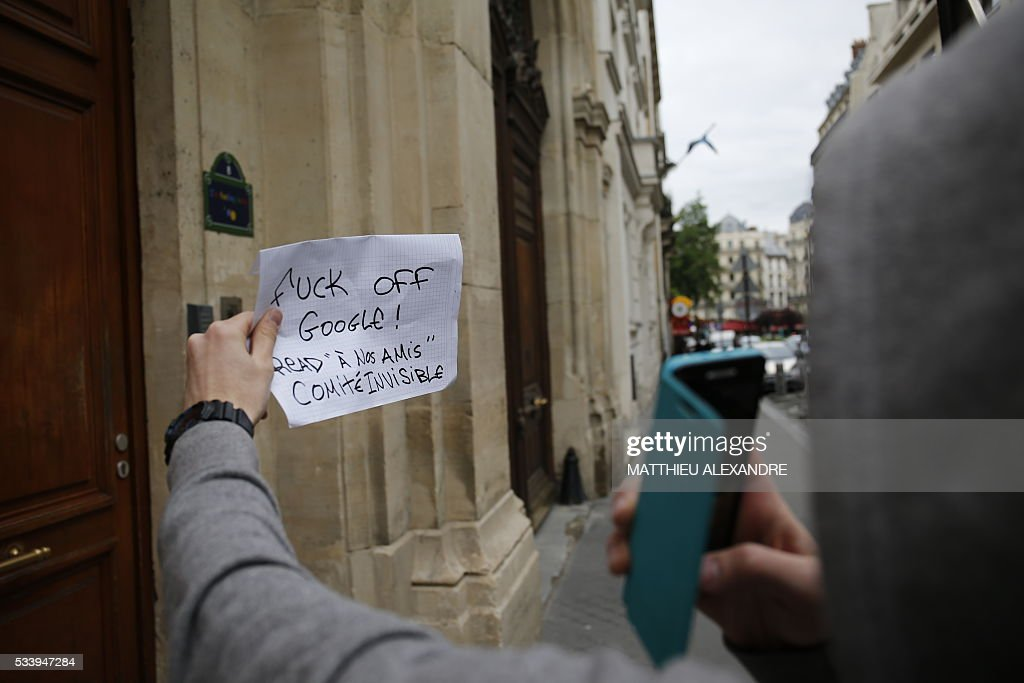 An individual takes a photograph while holding a sign reading 'Fuck off Google! Read 'To Our Friends' (by) The Invisible Committee' in front of the Google Paris offices on May 24, 2016 in Paris. French investigators swarmed Google's Paris offices on May 24 as part of a tax fraud investigation, with the US Internet giant saying it is 'cooperating fully' with the probe. French authorities believe Google owes 1,6 billion euros (USD 1,7 billion) in back taxes, a source close to the matter said in February. Google is one of several multinational corporations that have come under fire in Europe for paying extremely low taxes by shifting revenue across borders in an often complex web of financial arrangements.