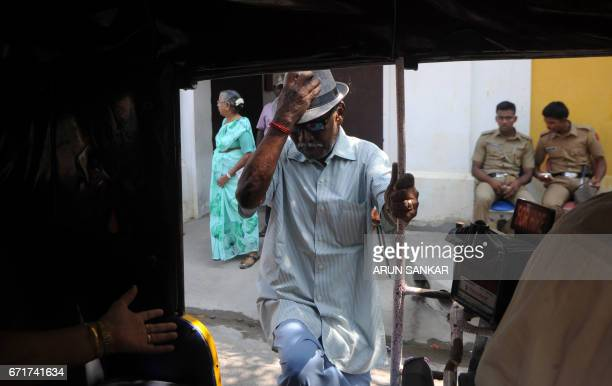 An IndoFrench citizen gestures as he enters an autorickshaw outside a polling station in Puducherry on April 23 after casting his vote during the...