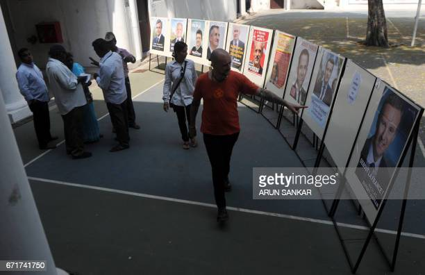 An IndoFrench citizen gestures at a display of portraits of French presidential candidates on the premises of a polling booth in Puducherry on April...