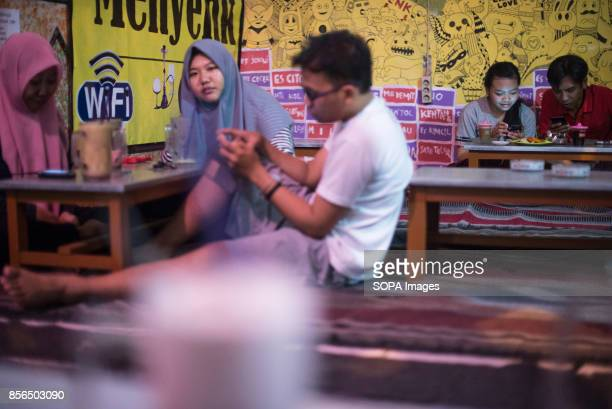 A 'WARKOP' IN SURABAYA EAST JAVA SURABAYA INDONESIA An Indonesia couple is seen drinking milk tea at a Warkop after school ended 'Warkop' is the name...