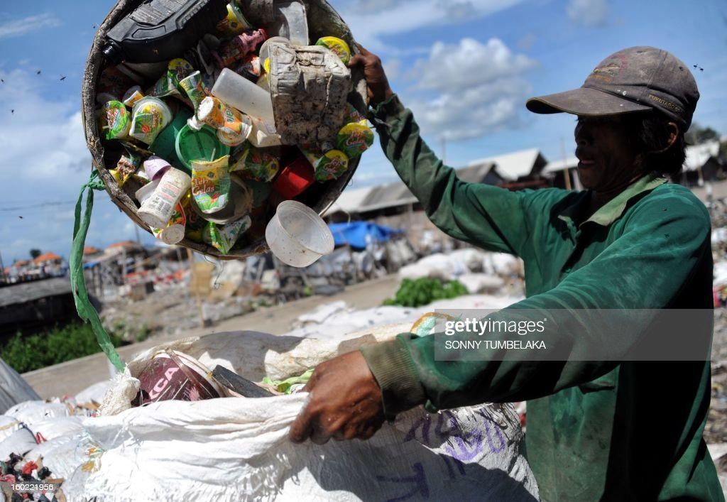 An Indonesia scavenger collects plastic bottles at a garbage dump in Denpasar on the island of Bali on January 28, 2013. AFP PHOTO/Sonny TUMBELAKA