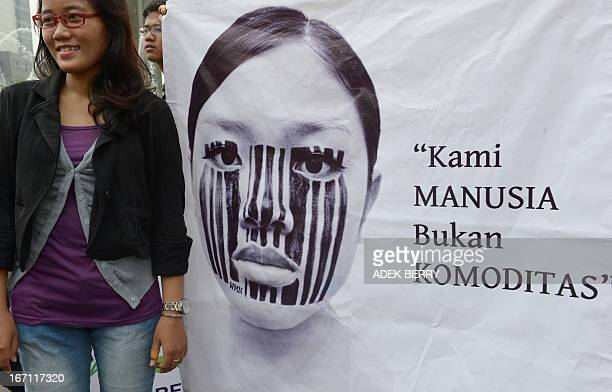An Indonesian activist stands next to a banner that reads 'We are human beings not commodities' during a peaceful protest against sexual abuse...