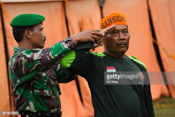 An Indonesian Banser recruit gets help in perfecting his salute by an Indonesian soldier brought in to teach parade drill during a three day...