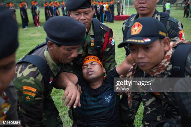 An Indonesian Banser recruit passes out after an exhausting obstacle course during a three day induction course on July 21 2017 in Kebumen Indonesia...