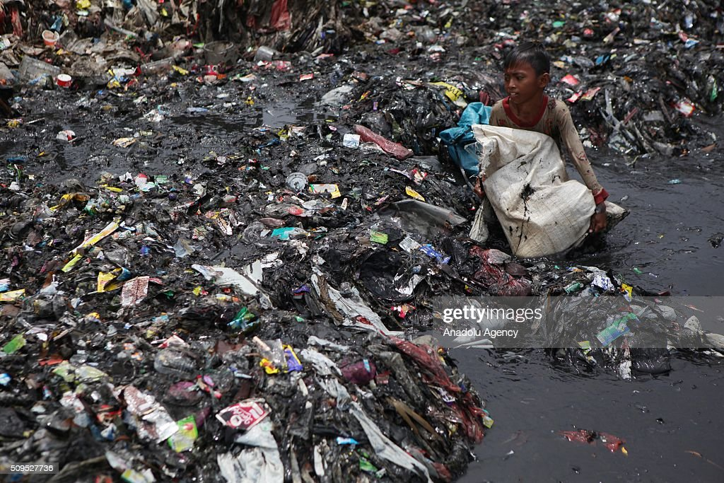 An Indonesian child collects garbages on the coast near a fishing village in Jakarta, Indonesia, on February 11, 2016. According to scientists 8 million metric tones of plastic pollution enter the oceans each year from the world's 192 coastal countries based on 2010 data.