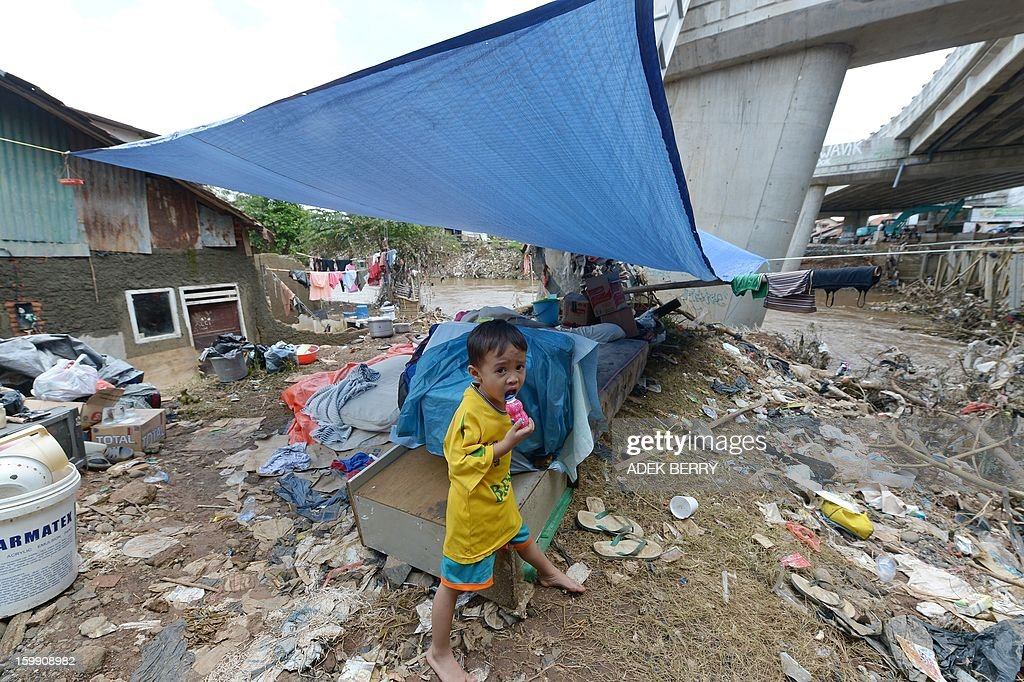 An Indonesian child stands next to a makeshift tent following heavy floods in Jakarta on January 23, 2013. A spokesman for Indonesian National Disaster Mitigation Agency (BNPB) said more than 30,000 people were still living as refugees on January 22, while 20 people were killed during the widespread flooding that hit Jakarta last week.