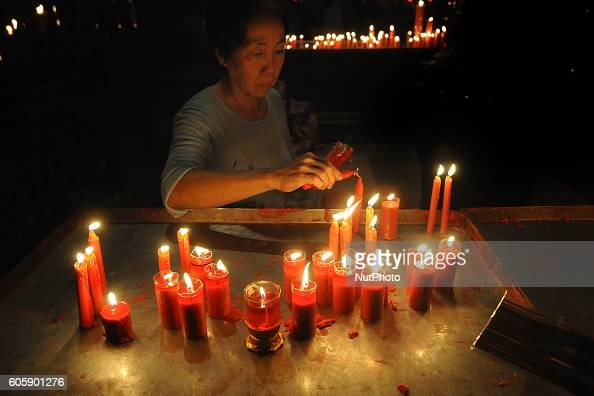 An Indonesian Chinese lights candles during Moon Cake Festival at Sanggar Agung Temple Kenjeran on September 15 2016 in Surabaya Indonesia The Moon...