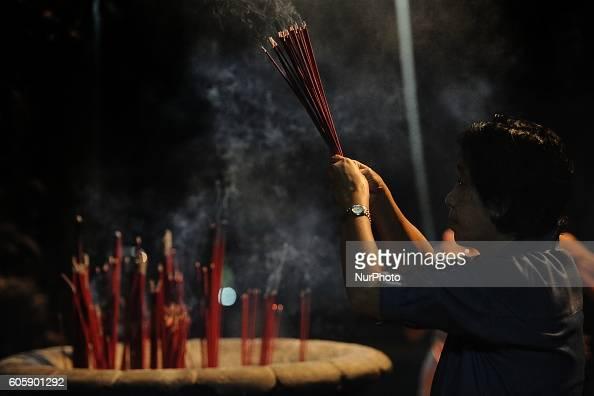 An Indonesian Chinese prays holding incense sticks during Moon Cake Festival at Sanggar Agung Temple Kenjeran on September 15 2016 in Surabaya...