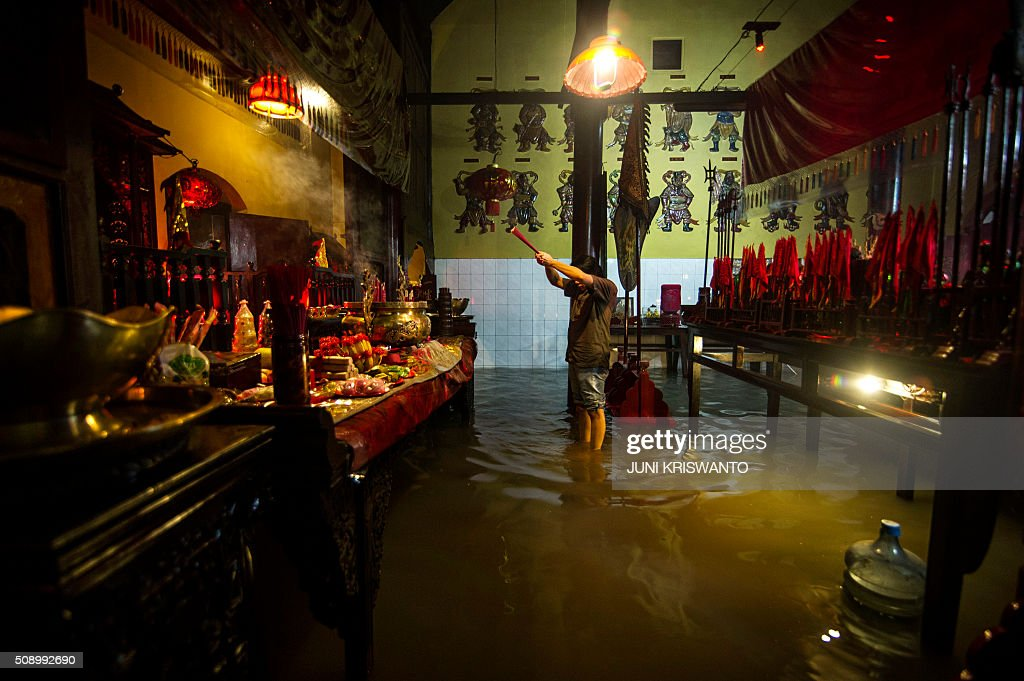 An Indonesian Chinese stands in flood waters caused by monsoon rains two days previously to pray at a temple to mark the first day of the Lunar New Year in Sidoarjo on February 8, 2016. After decades of repression under the dictatorship of Suharto, who rose to power after a bloody purge of communists and Chinese in the late 1960s, Chinese-Indonesians are now accepted in mainstream society of the largely Muslim nation, with the Lunar New Year - this year marking the Year of the Monkey - a public holiday where it is known as 'Imlek'. AFP PHOTO / JUNI KRISWANTO / AFP / JUNI KRISWANTO