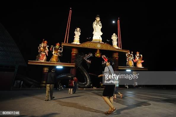 An Indonesian Chinese walks holding incense sticks as she pray during Moon Cake Festival at Sanggar Agung Temple Kenjeran on September 15 2016 in...