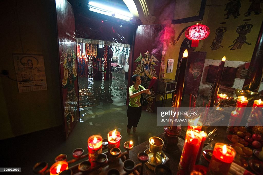 An Indonesian Chinese woman holds up incense as she stands in flood waters caused by monsoon rains two days previously to pray at a temple to mark the first day of the Lunar New Year in Sidoarjo on February 8, 2016. After decades of repression under the dictatorship of Suharto, who rose to power after a bloody purge of communists and Chinese in the late 1960s, Chinese-Indonesians are now accepted in mainstream society of the largely Muslim nation, with the Lunar New Year - this year marking the Year of the Monkey - a public holiday where it is known as 'Imlek'. AFP PHOTO / JUNI KRISWANTO / AFP / JUNI KRISWANTO