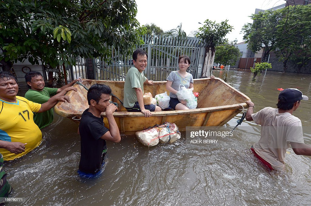 An Indonesian couple rides a rented makeshift raft to travel down a flooded street at a luxury housing complex in Jakarta on January 20, 2013. The death toll from floods in Indonesia's capital Jakarta rose to 15 on January 19 after rescuers found another four bodies. The floods are the worst to hit the capital since 2007 and forced 18,000 people from their homes.