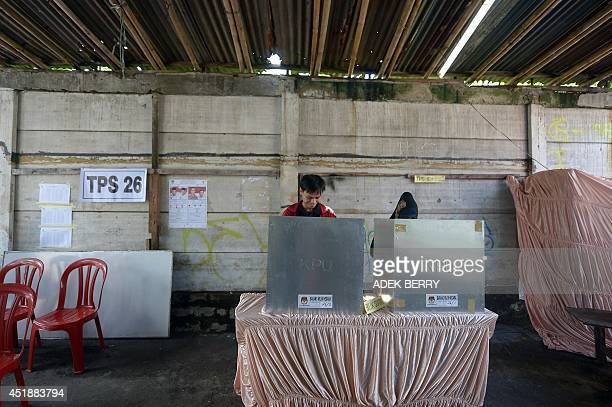 An Indonesian couple votes in the country's presidential election at a makeshift polling centre in Jakarta on July 9 2014 Indonesians voted on July 9...