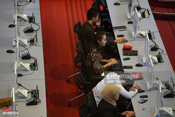 An Indonesian employee of the Indonesia Stock Exchange takes a nap while others work in Jakarta on July 10 2014 Indonesian stocks rallied to a...