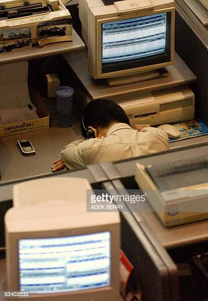 An Indonesian employee of the Jakarta stock exchange takes a nap during trading in Jakarta 18 August 2005 Indonesian share prices closed 121 percent...