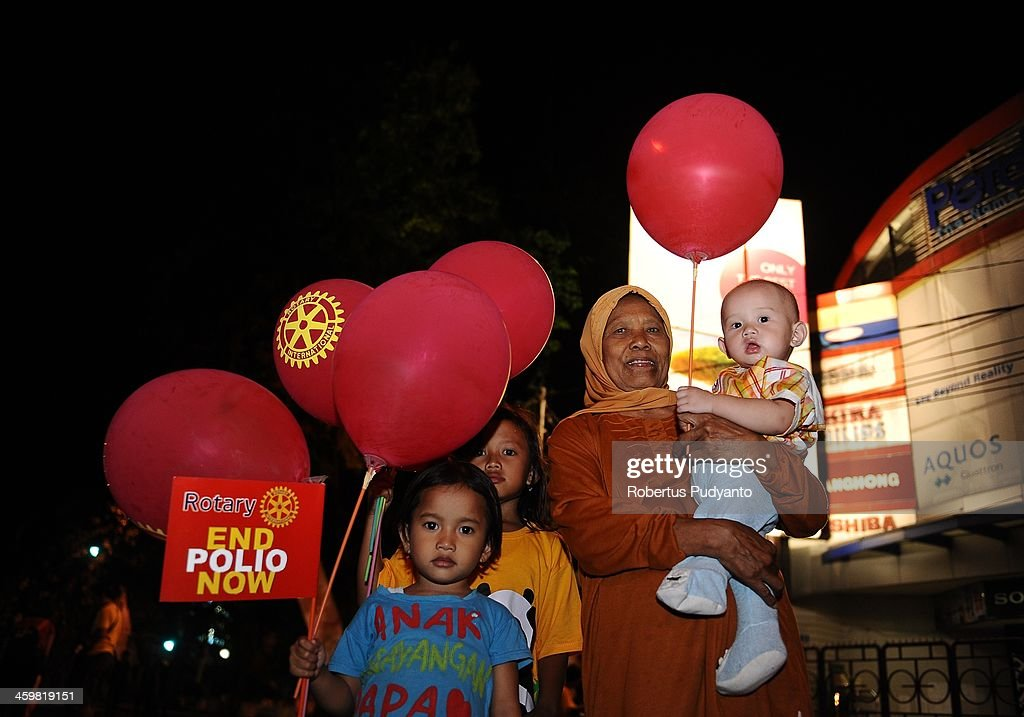 An Indonesian family gathers at the city park to celebrate 2014 New Years on December 31, 2013 in Surabaya, Indonesia. A wave of pyrotechnic displays kicked off New Years celebrations in major cities around the world.