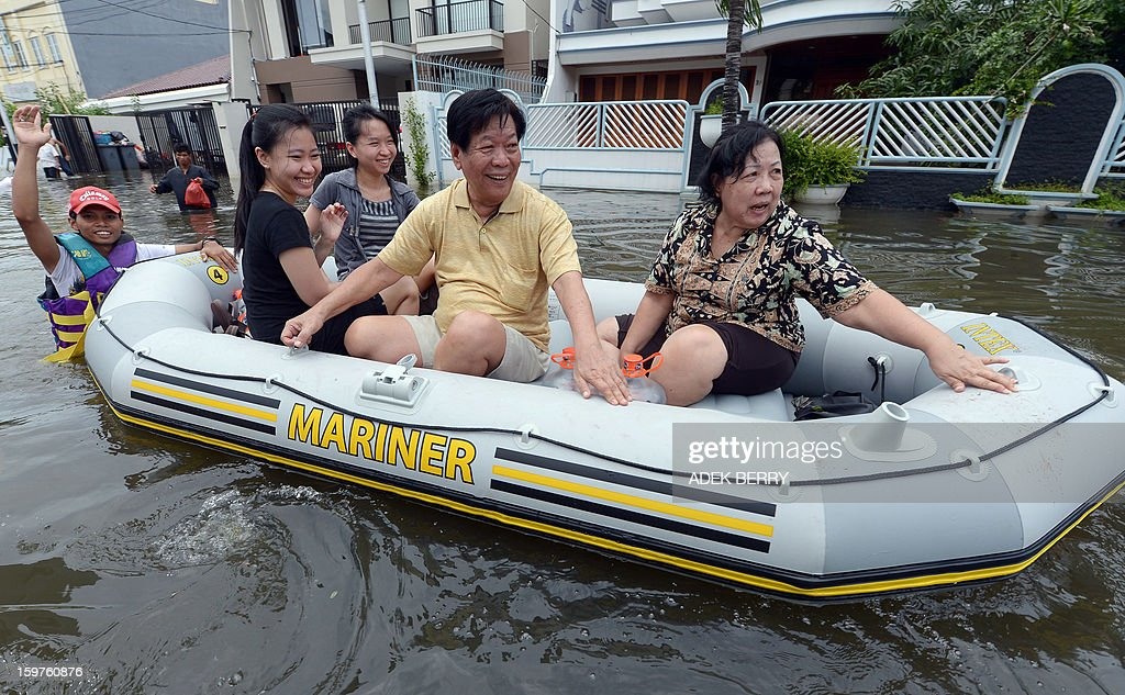 An Indonesian family rides in a rubber dingny down a flooded street at a luxury housing complex in Jakarta on January 20, 2013. The death toll from floods in Indonesia's capital Jakarta rose to 15 on January 19 after rescuers found another four bodies. The floods are the worst to hit the capital since 2007 and forced 18,000 people from their homes.