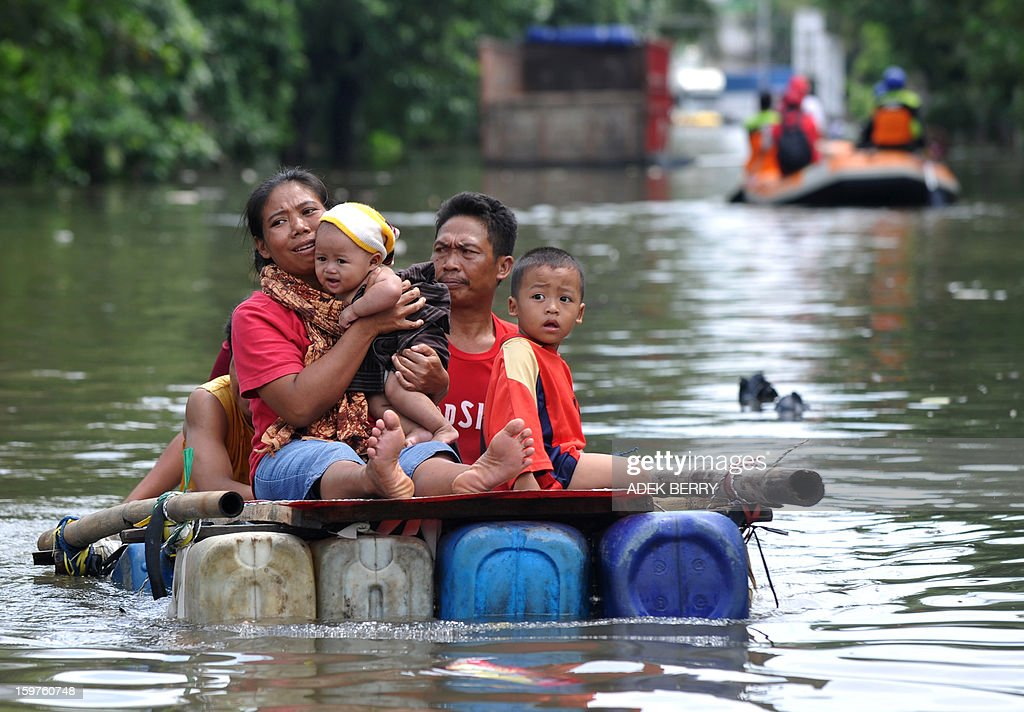 An Indonesian family uses a makeshift raft as they wade down a flooded street in Jakarta on January 20, 2013. The death toll from floods in Indonesia's capital Jakarta rose to 15 on January 19 after rescuers found another four bodies. The floods are the worst to hit the capital since 2007 and forced 18,000 people from their homes.