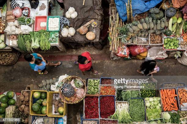 An Indonesian female porter carries a basket of vegetables and meats on her head at Badung traditional market on March 8 2014 in Denpasar Bali...