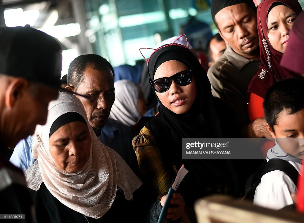An Indonesian girl (C) wearing a cat-ear headband waits with her family to board a ferry to head home ahead of the Eid al-Fitr festival at the port passenger terminal in Port Klang on July 2, 2016. A large number of Indonesians living in Malaysia head back home to celebrate Eid Al-fitr festival with their families during the last days of the fasting month of Ramadan. / AFP / MANAN