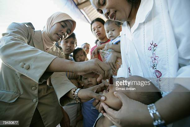 An Indonesian health worker vaccinates an Indonesian child against polio after measles immunisation February 27 2007 in Jakarta Indonesia Indonesia...