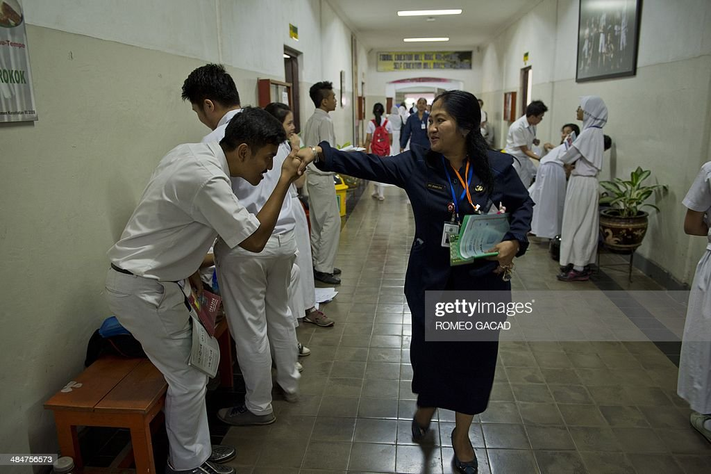 An Indonesian high school student greets a teacher on the first day of national examinations at a state senior high school in Jakarta on April 14, 2014. More than a million students will take part in state senior high school final examinations across Indonesia's 17,000 islands that students are required to pass in order to graduate and continue to higher studies in colleges and universities.