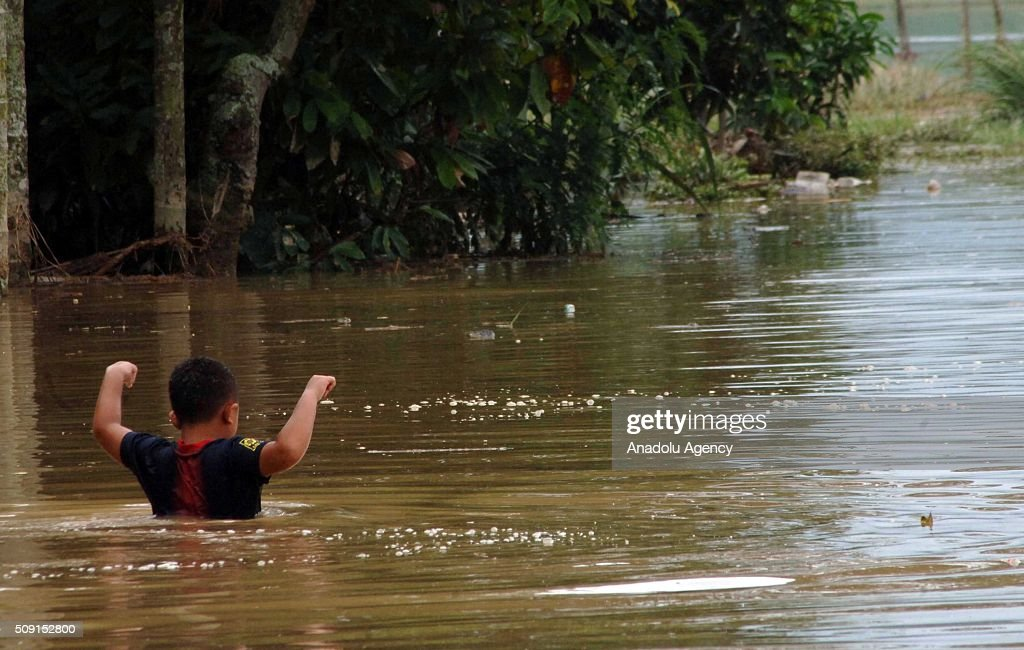 An Indonesian kid saves himself from floods at Pangkalan village on February 09, 2016 in Lima Puluh Koto regency, West Sumatra Province, Indonesia. More 1000 houses submerged, 5000 residents were evacuated.
