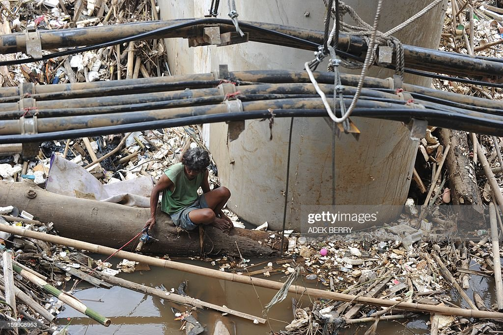 An Indonesian man fishes at the Ciliwung river full of garbages following heavy floods in Jakarta on January 23, 2013. A spokesman for Indonesian National Disaster Mitigation Agency (BNPB) said more than 30,000 people were still living as refugees on January 22, while 20 people were killed during the widespread flooding that hit Jakarta last week. AFP PHOTO / ADEK BERRY