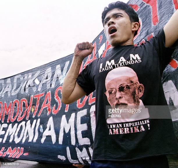An Indonesian man from one of Indonesia's Muslim hardline groups shout slogans in support of Abu Bakar Bashir outside the court in Jakarta 23 April...
