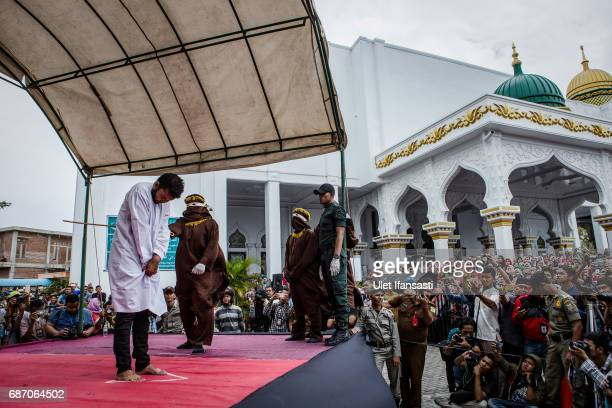 An Indonesian man gets caning in public from an executor known as 'algojo' for having gay sex which is against Sharia law at Syuhada mosque on May 23...