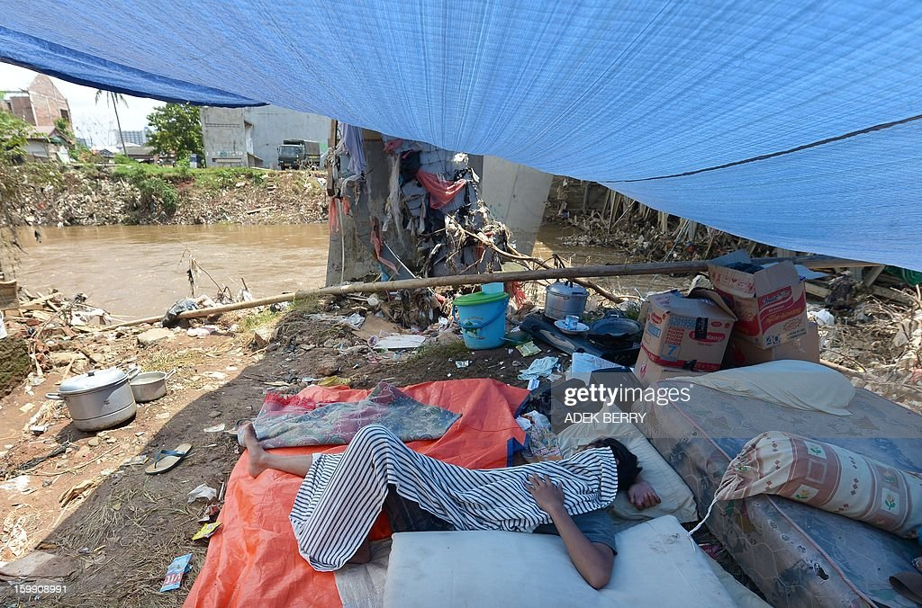 An Indonesian man lies down in a makeshift tent next to the Ciliwung river following heavy floods in Jakarta on January 23, 2013. A spokesman for Indonesian National Disaster Mitigation Agency (BNPB) said more than 30,000 people were still living as refugees on January 22, while 20 people were killed during the widespread flooding that hit Jakarta last week. AFP PHOTO / ADEK BERRY