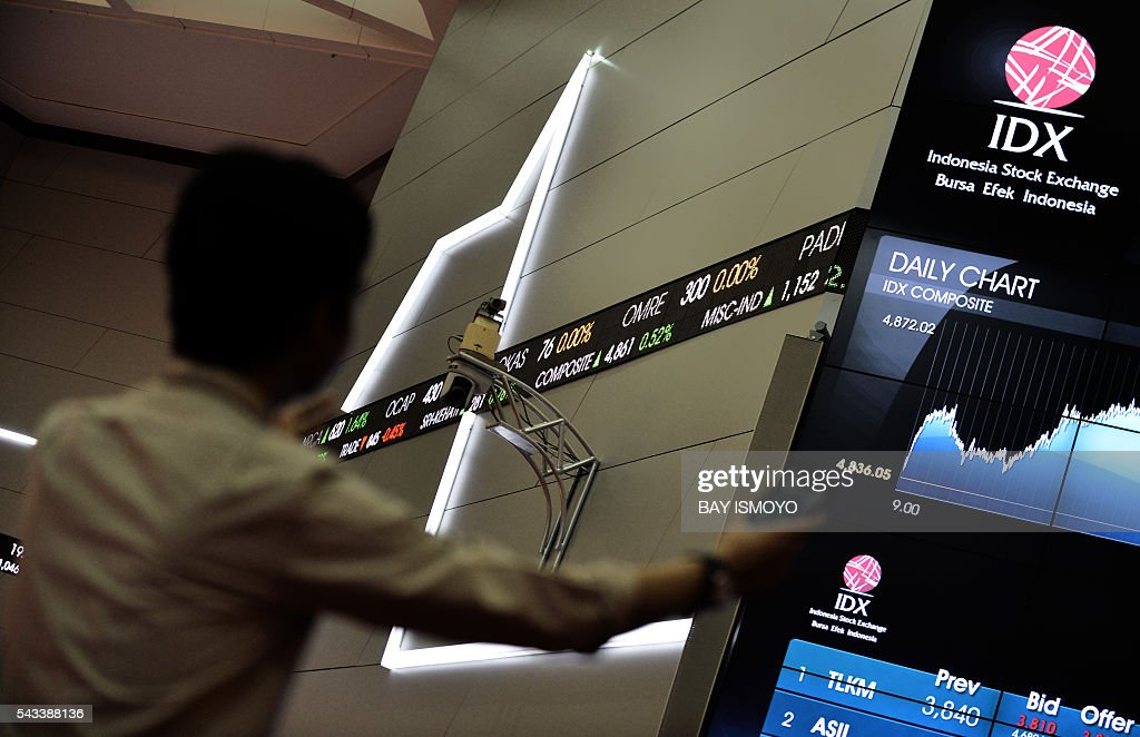 An Indonesian man looks at the stock exchange share prices board in Jakarta on June 28, 2016. Asia led a bounce in world markets on June 28 while the pound rose as traders began betting on a fresh round of stimulus to mitigate the effects of Britain's shock decision to leave the EU. / AFP / BAY