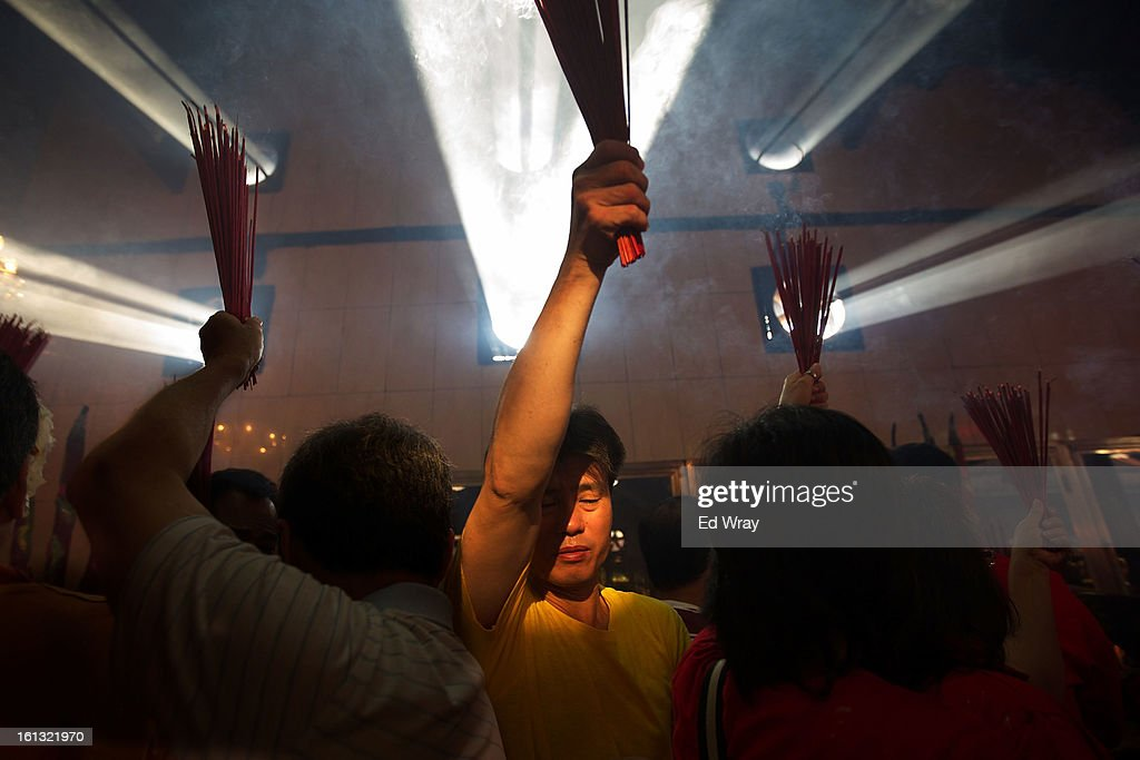 An Indonesian man of Chinese descent carries joss sticks through the smoke filled Vihara Dharma Bhakti temple on the first day of the Chinese Lunar New year February 10, 2013 in Jakarta, Indonesia. Chinese people around the world are ushering in the Year of the Snake with prayers, feasts and fireworks.